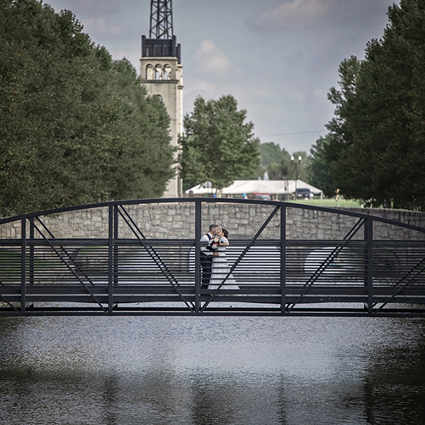 Shane Michael Studios Wedding Photography of bride and groom standing on a bridge overlooking a lake