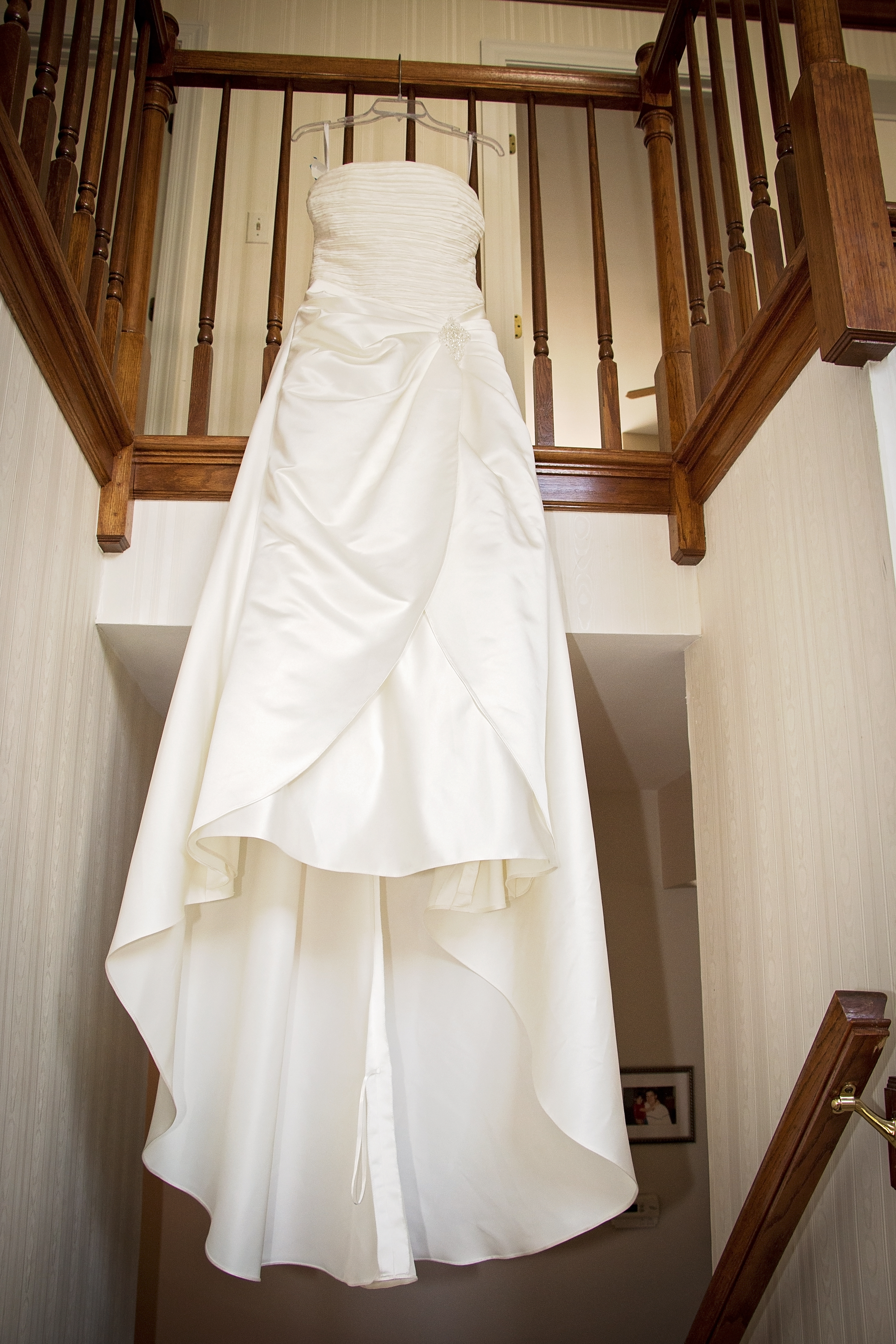 Photo of a wedding gown hanging from the staircase