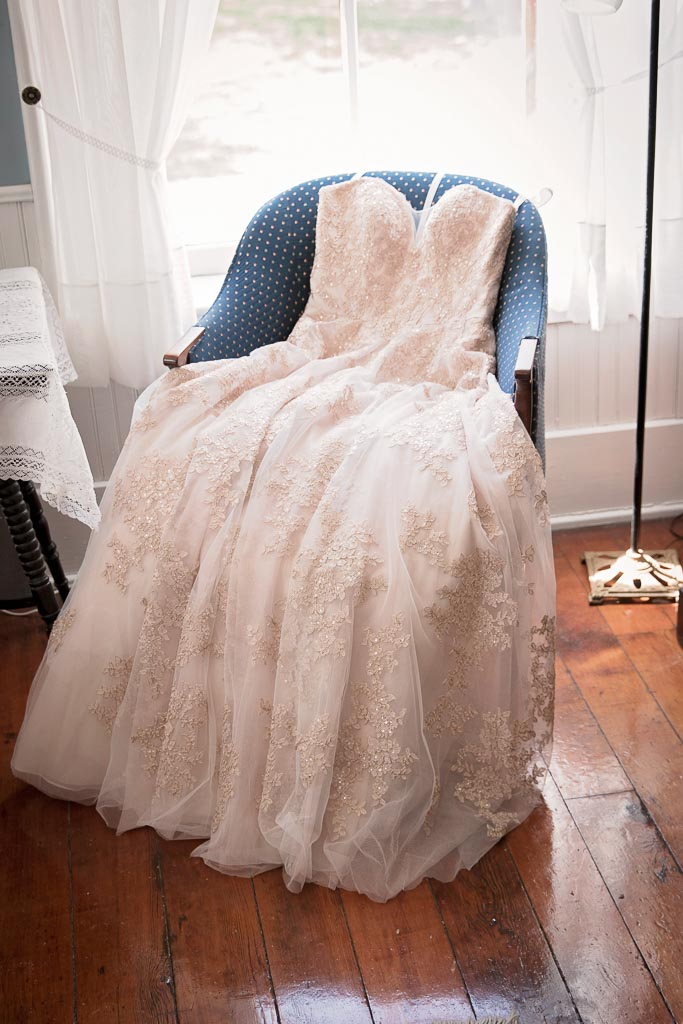 wedding dress laying on chair by window