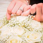 holding hands of bride and groom over flowers