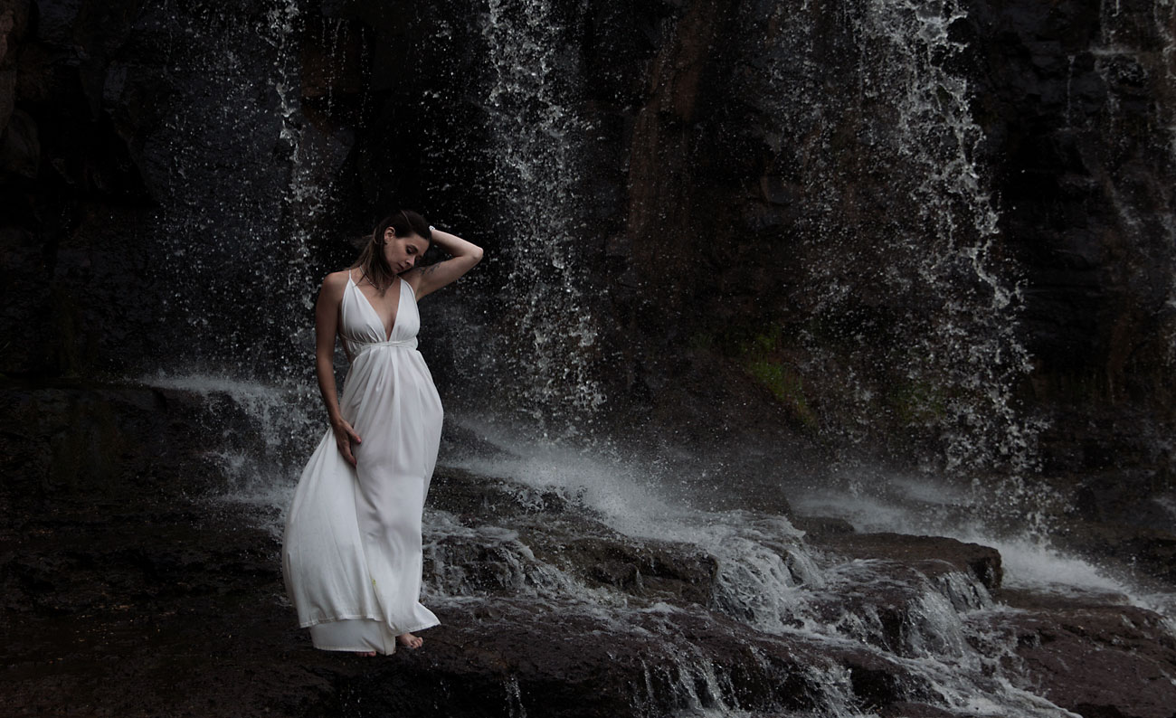 Bride standing in front of a waterfall