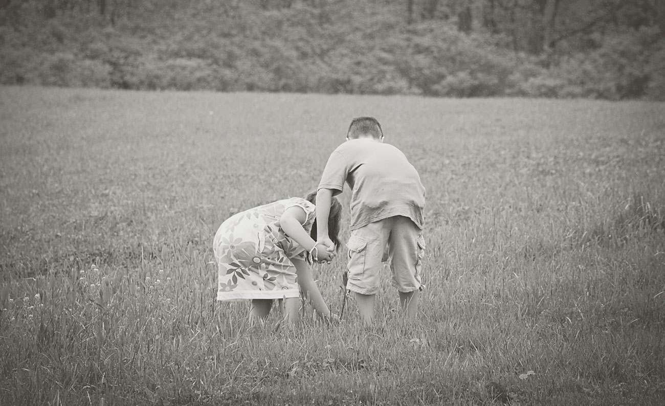 Young girl and boy holding hands and playing in a field of grass