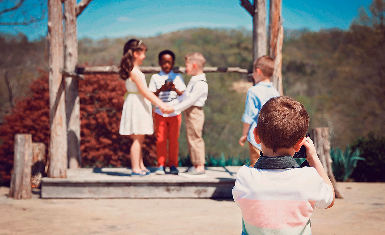 Group of children pretending their having a wedding