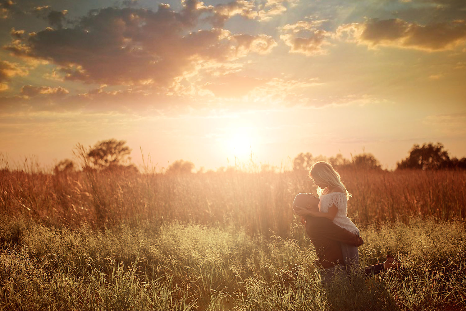 engagement photo of couple in a field during sunset