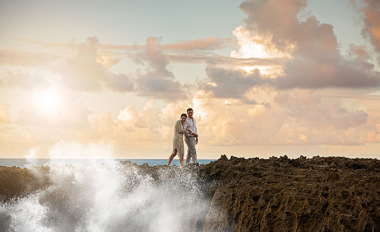 wedding couple on rocks with ocean and sunset